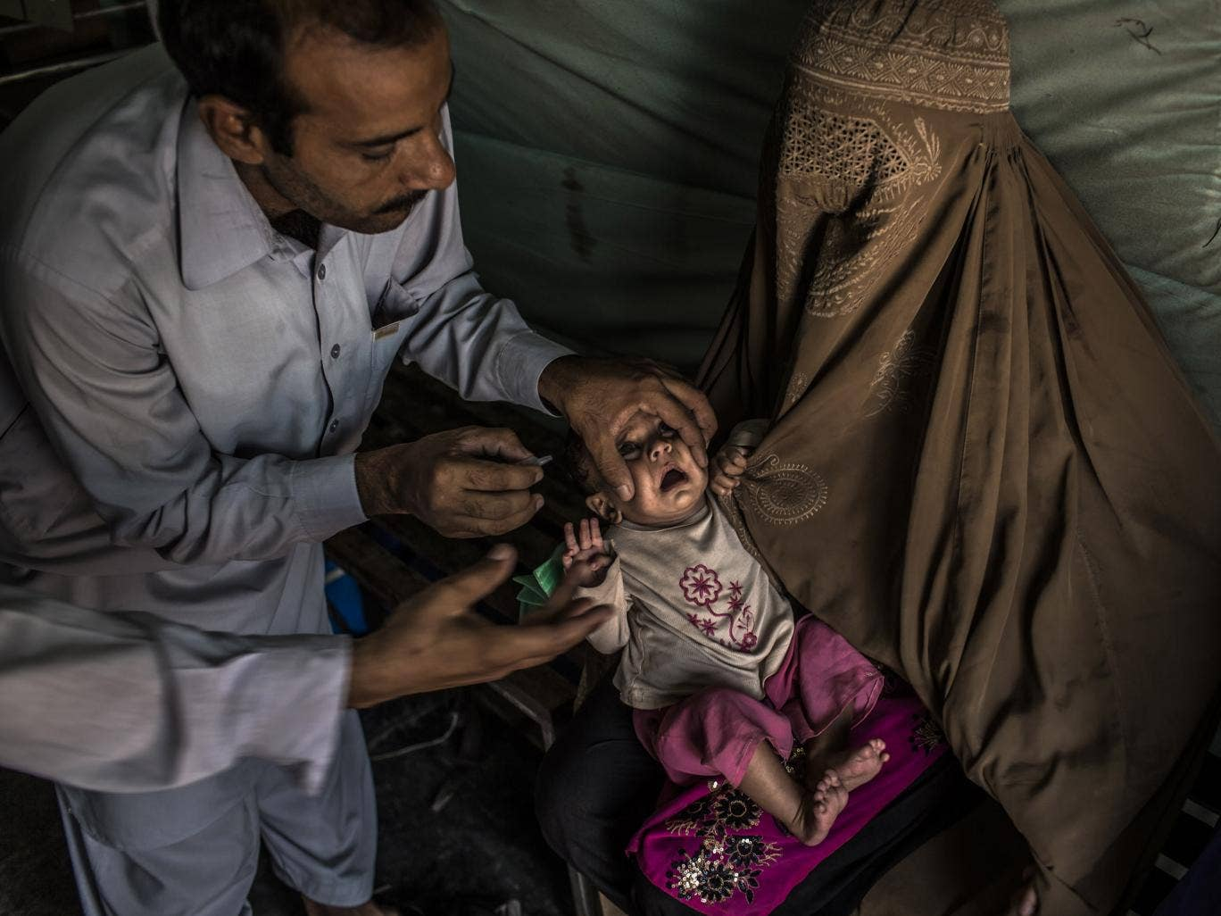 A child in Pakistan is given the polio vaccination
