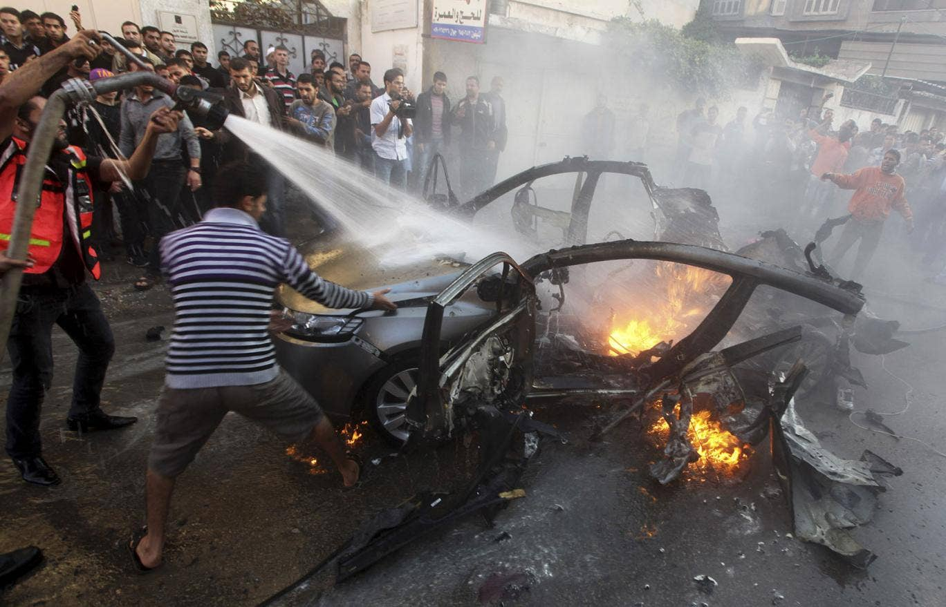 Palestinians extinguish fire from the car of Ahmed al-Jabari after it was hit by one of several Israeli air strikes in Gaza City
