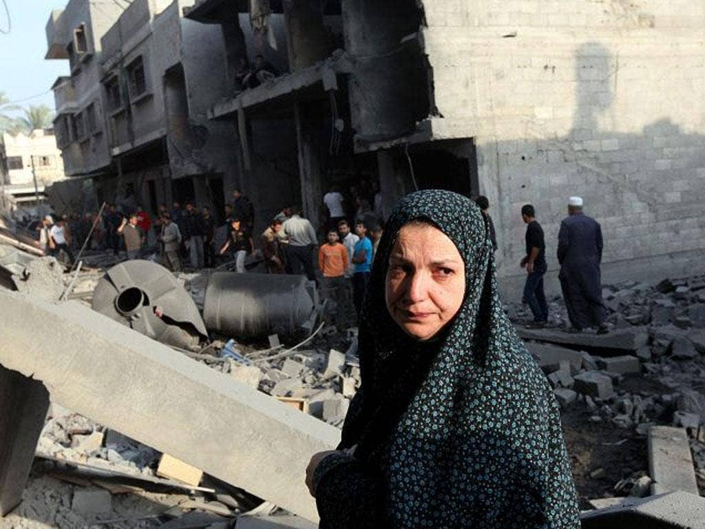 A Palestinian woman inspects the rubble of her destroyed house after an Israeli air strike in the east of Gaza city