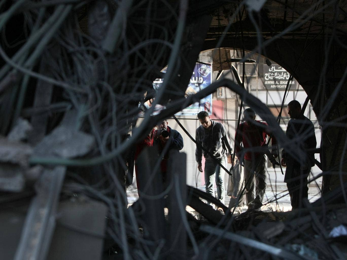 Palestinians inspect damage from an Israeli air strike
