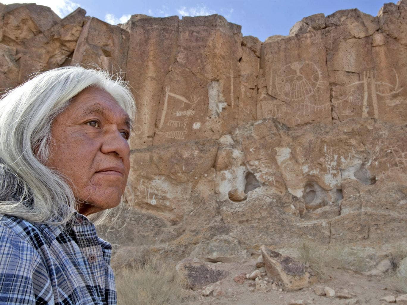 Raymond Andrews, the local tribal historical preservation officer, examines the damage