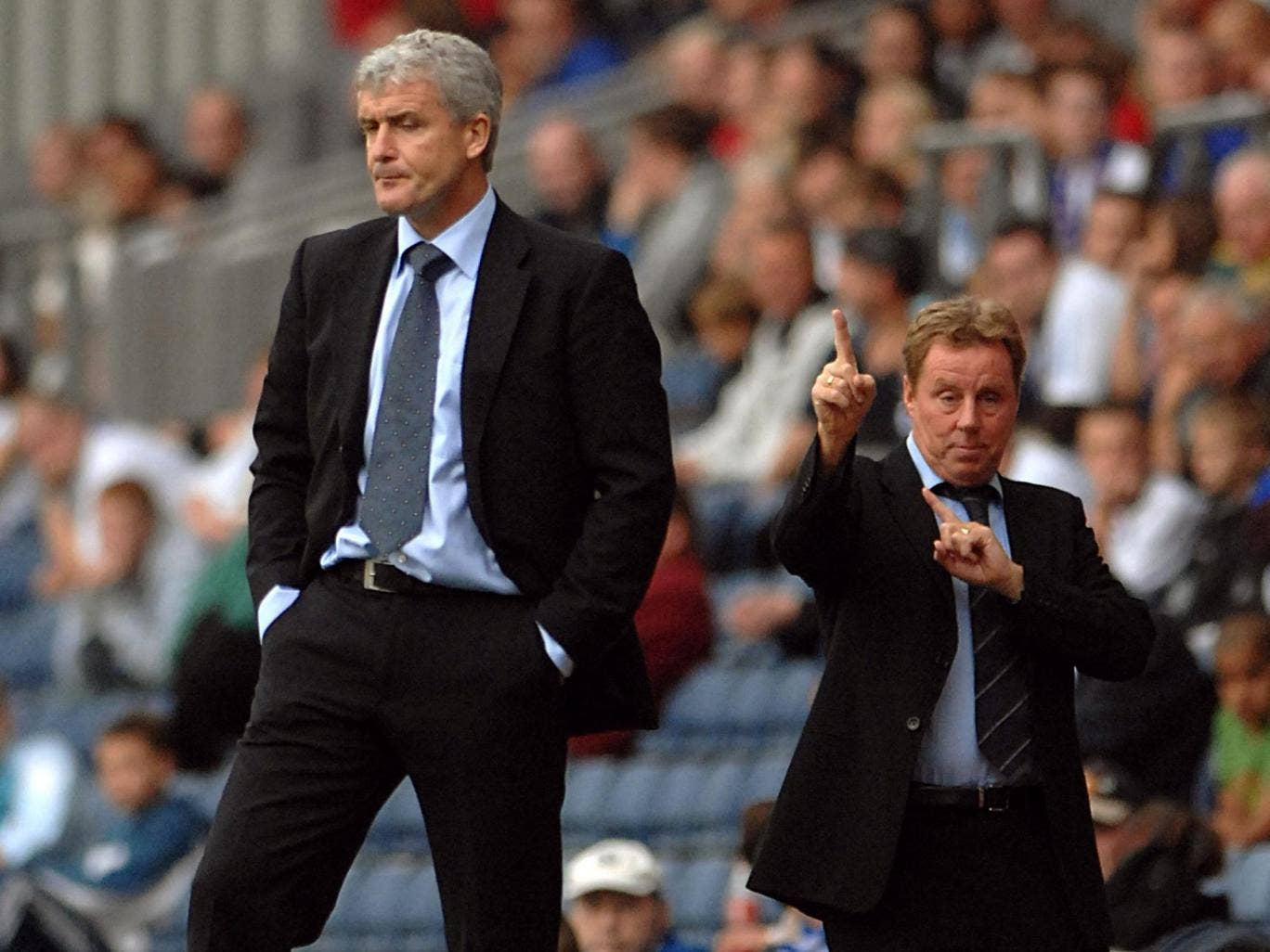 Harry Redknapp points the way ahead behind the back of Mark Hughes