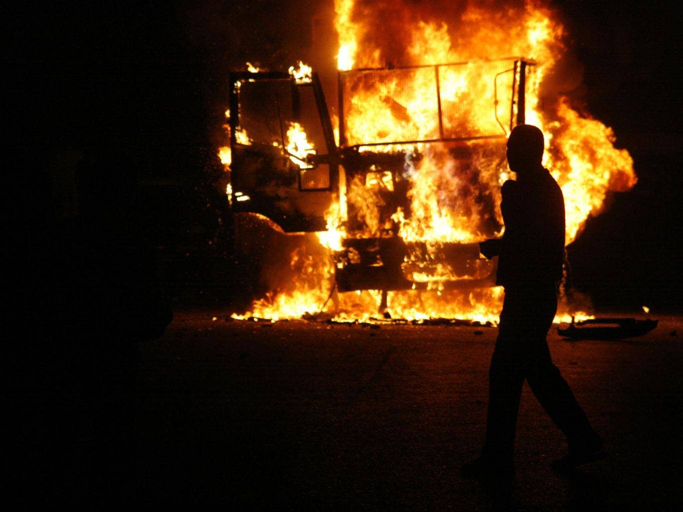 An Egyptian man walks by a burning Egyptian police truck during a demonstration against Egypt's Islamist President Mohamed Morsi on November 23, 2012 in Cairo. Morsi insisted that Egypt is on the path to 'freedom and democracy' after granting himself swee