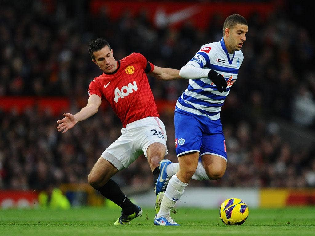 Robin van Persie of Manchester United competes with Adel Taarabt of Queens Park Rangers