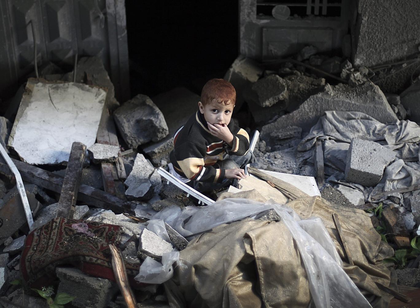 Destruction: A boy sits in a Gaza house wrecked by an Israeli air-strike