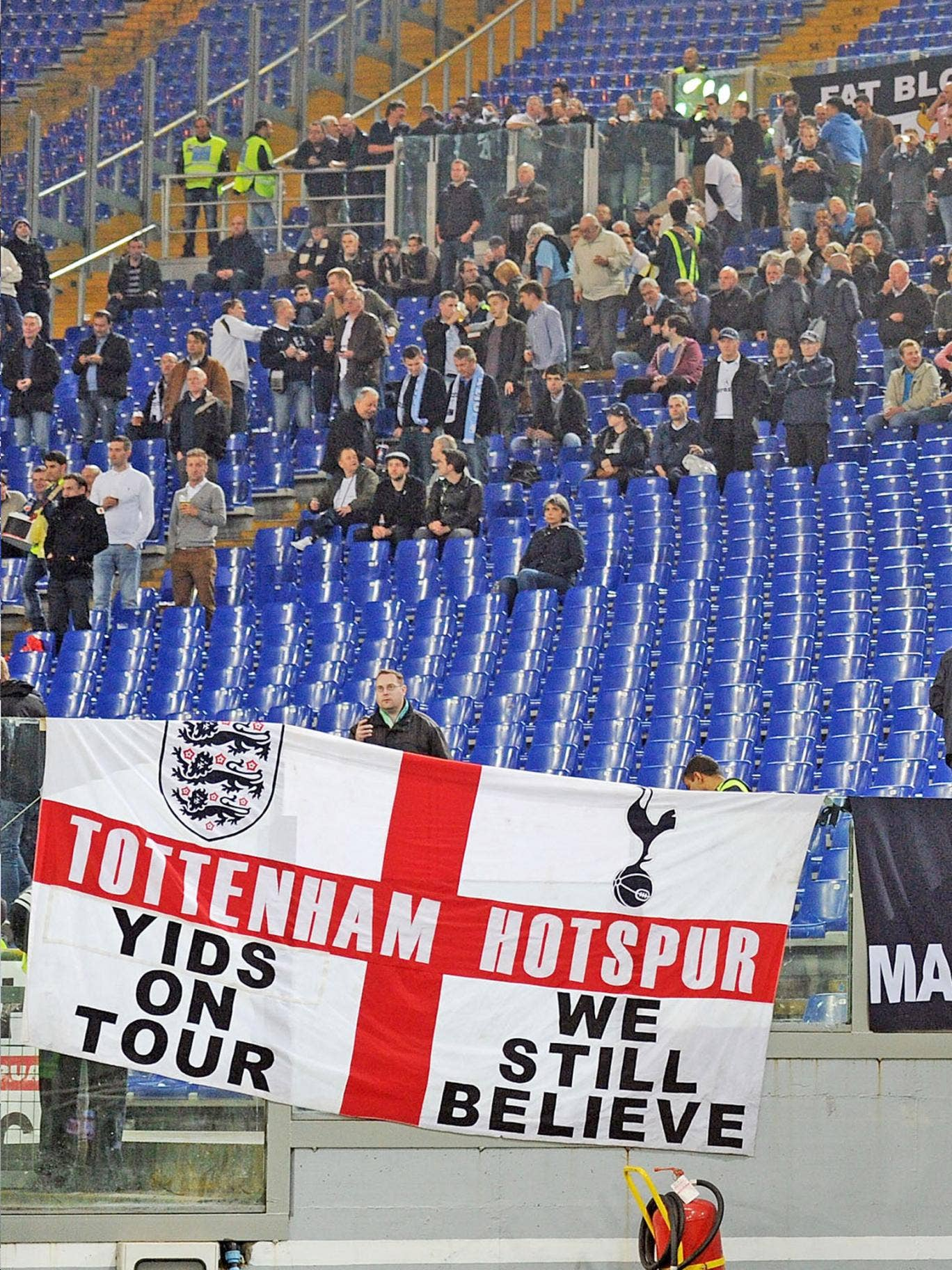 A section of Spurs fans rally behind a controversial banner