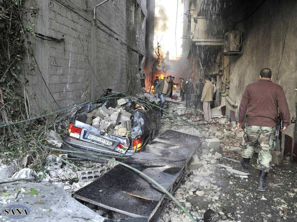 Twin car bombs have ripped through a Damascus suburb killing and wounding dozens of people