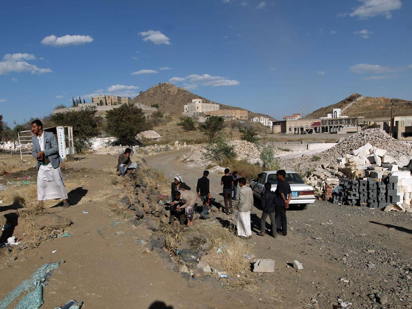 Yemeni men inspect the site where a Saudi diplomat and his bodyguard were killed in Sanaa's southern district of Hada, where embassies and diplomats' residences are located