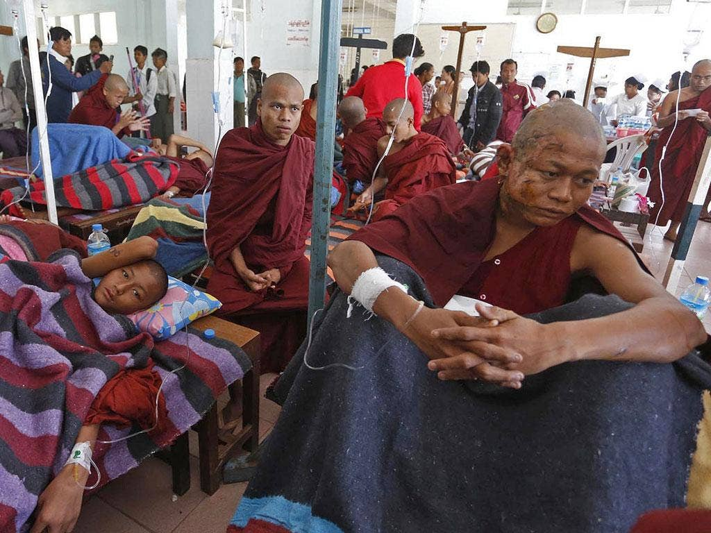 A severely burnt Buddhist monk receiving treatment after police fired water cannons and smoke bombs to break up protests