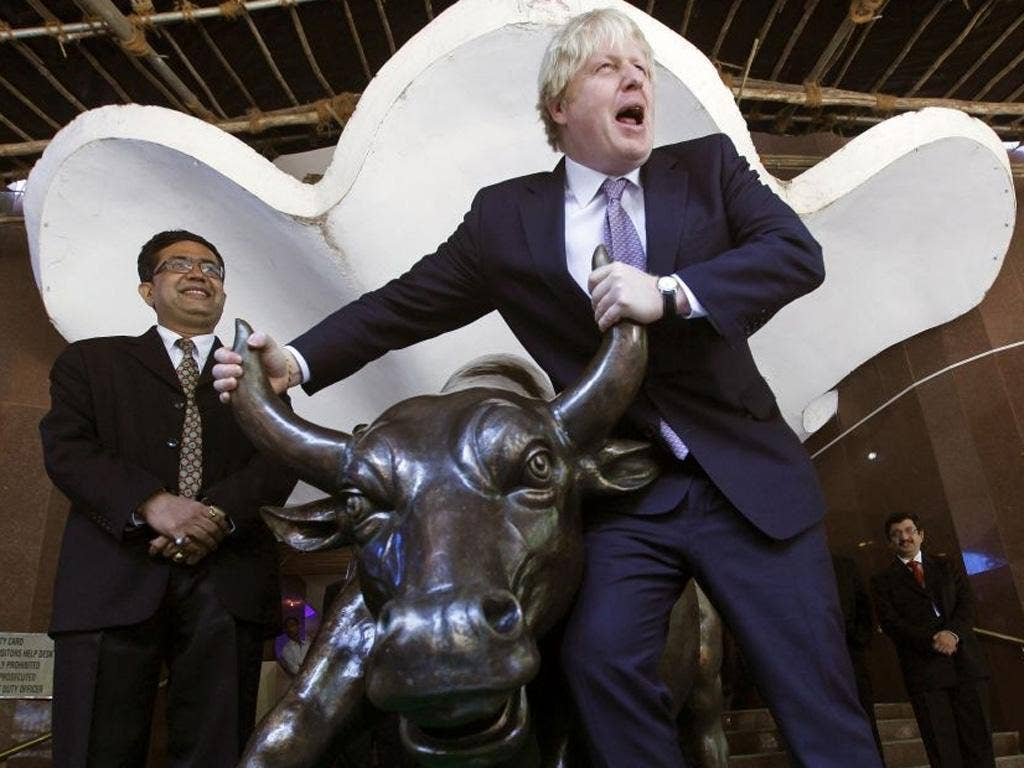 London Boris Johnson poses with the bronze statue of a bull outside the Bombay Stock Exchange