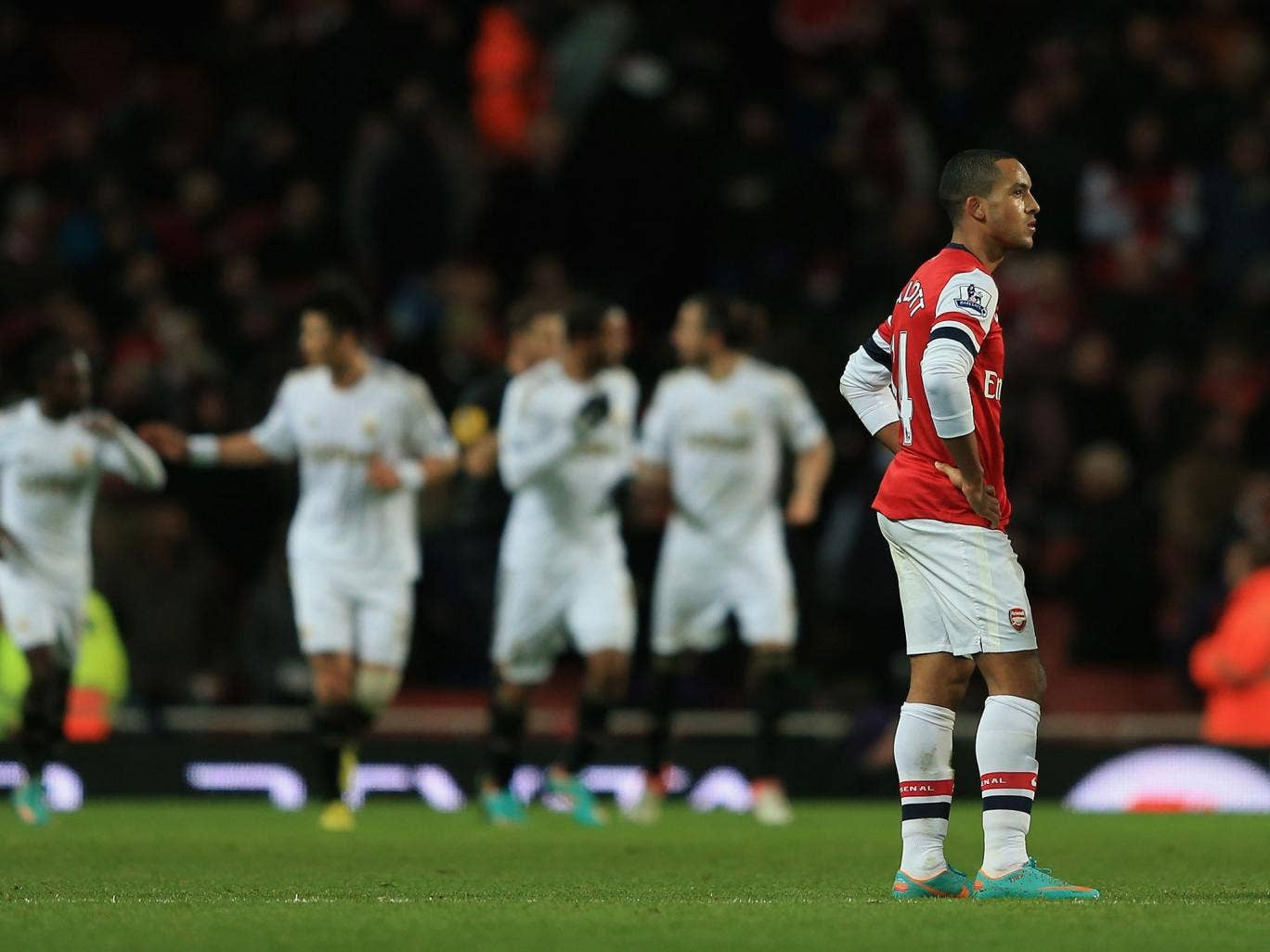 Theo Walcott looks upset after Swansea score their opening goal late in the second half