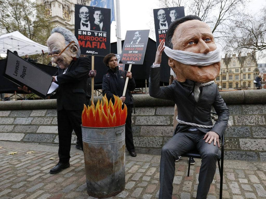 Burning issue: Protesters pose as Rupert Murdoch and David Cameron as the Leveson report comes out
