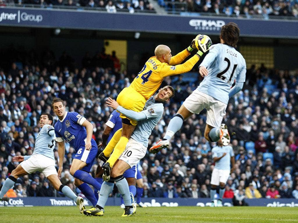 City's Edin Dzeko collides with Tim Howard on Saturday