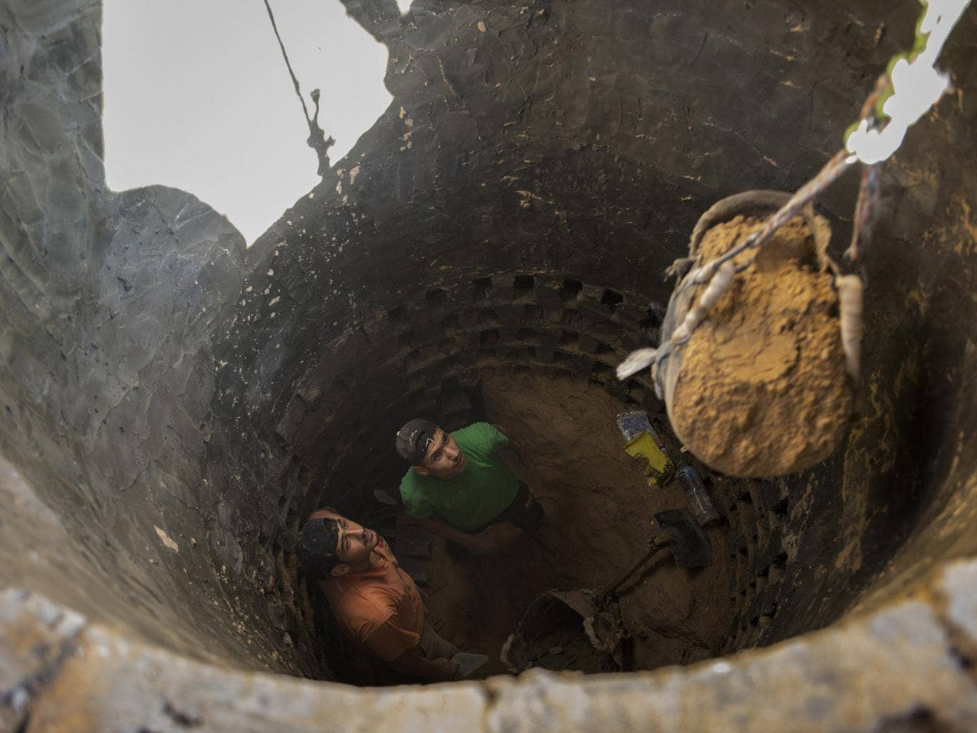 MIDEAST TUNNELS: Ismael al-Arja, 25, and Mahmoud al-Arja, 25, watch as a bucket of soil is hoisted out of the tunnel they are digging along the Egypt-Gaza border.