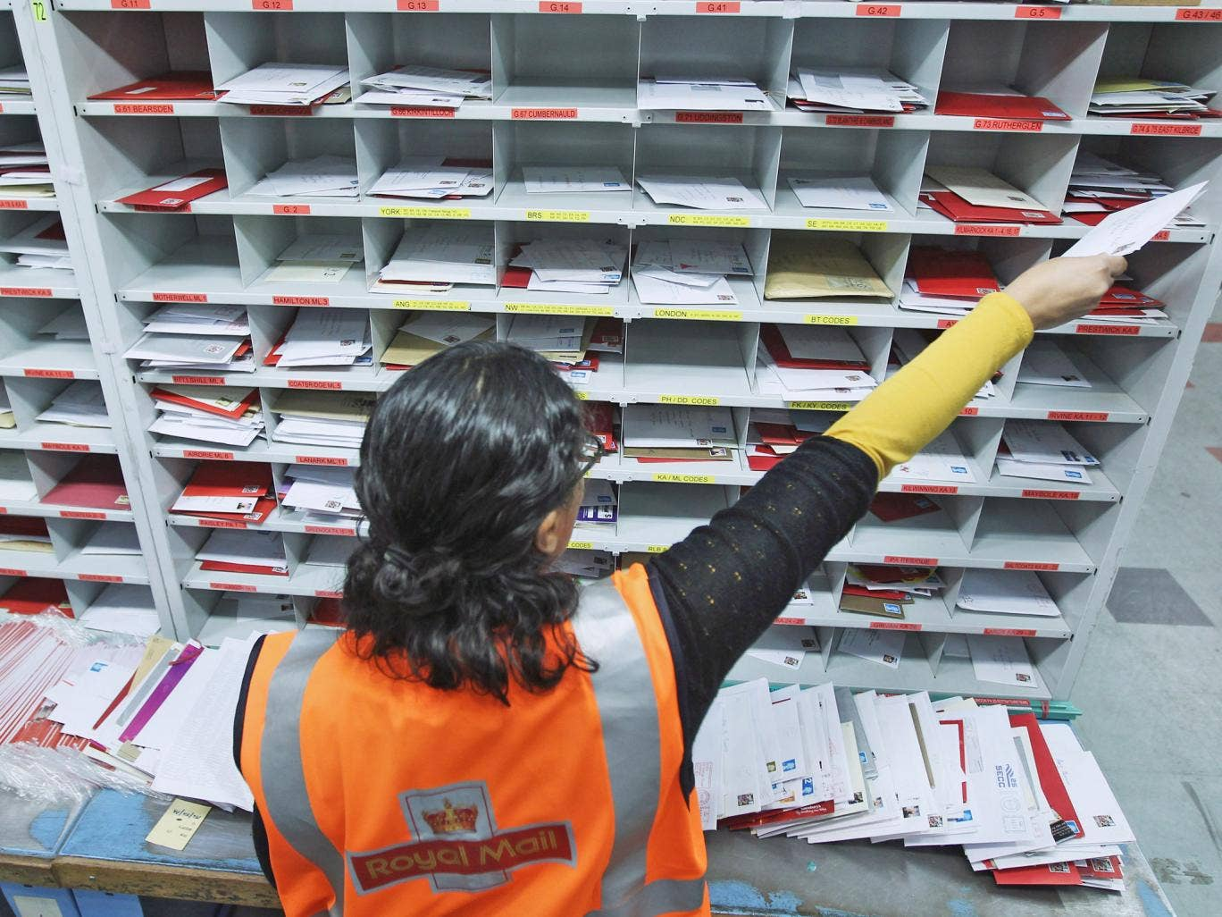 A Royal Mail worker handles mail at a sorting office
