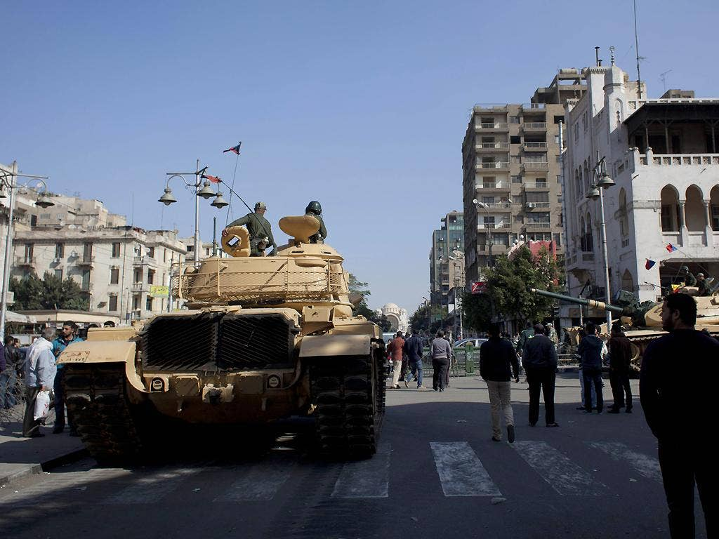 Egyptian Army tanks deploy near the presidential palace to secure the site of overnight clashes between supporters and opponents of President Mohammed Morsi in Cairo