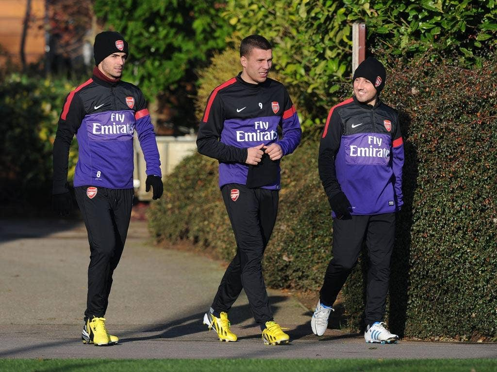 Mikel Arteta, Lukas Podolski and Santi Cazorla of Arsenal during a training session