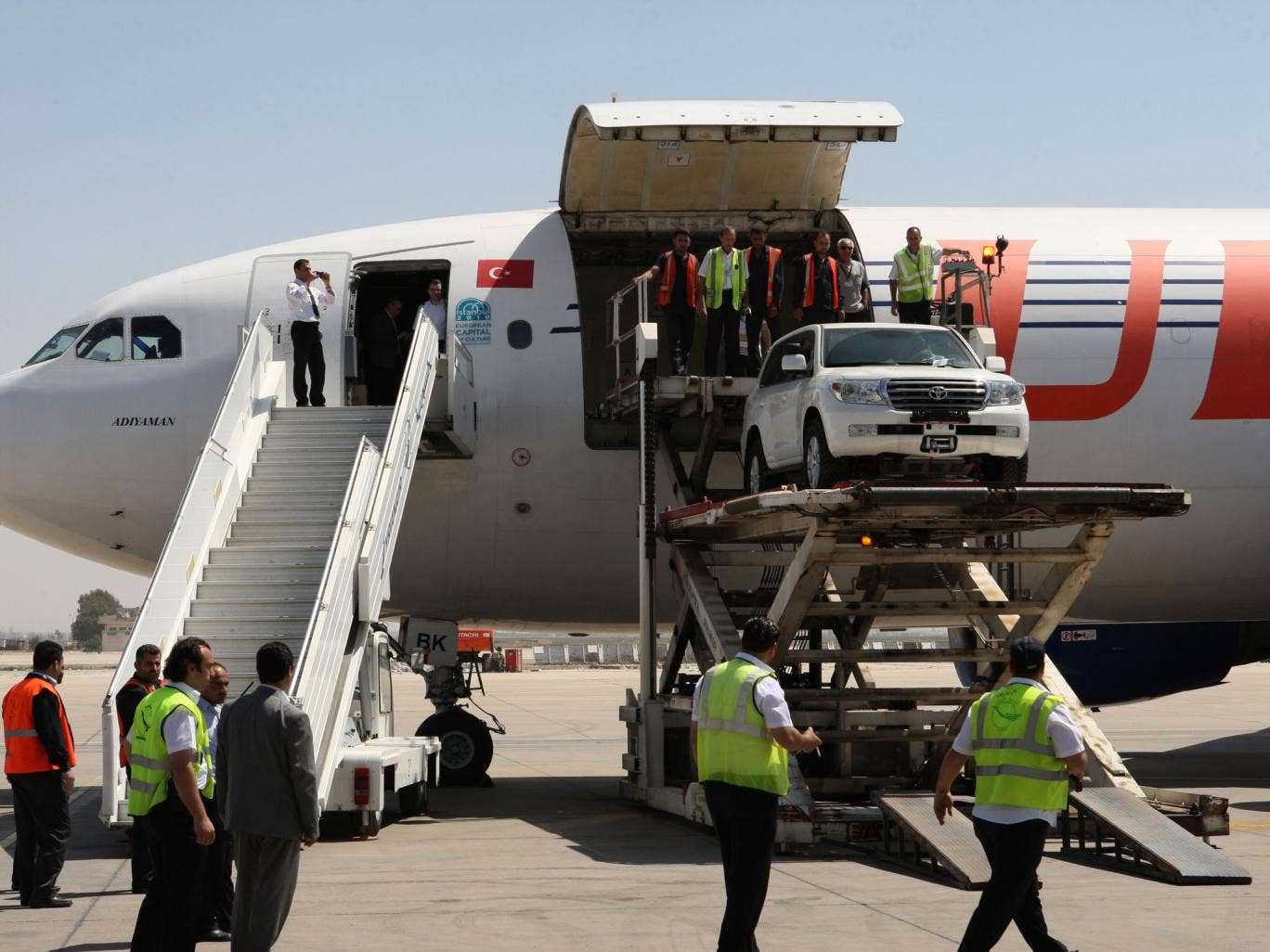 UN trucks are unloaded at Damascus airport