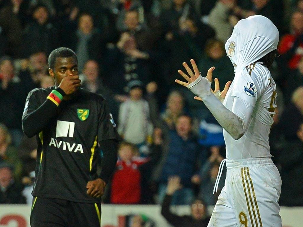 Sebastien Bassong of Norwich looks on as Swansea striker Michu celebrates a goal