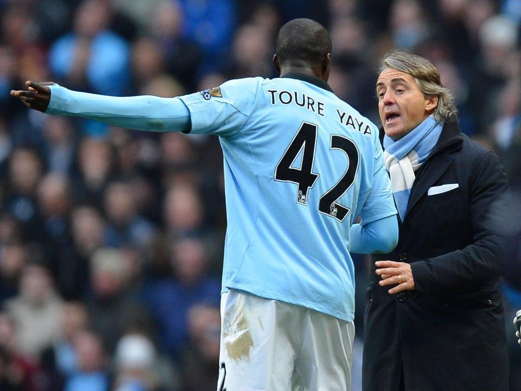 Yaya Toure talks with Roberto Mancini