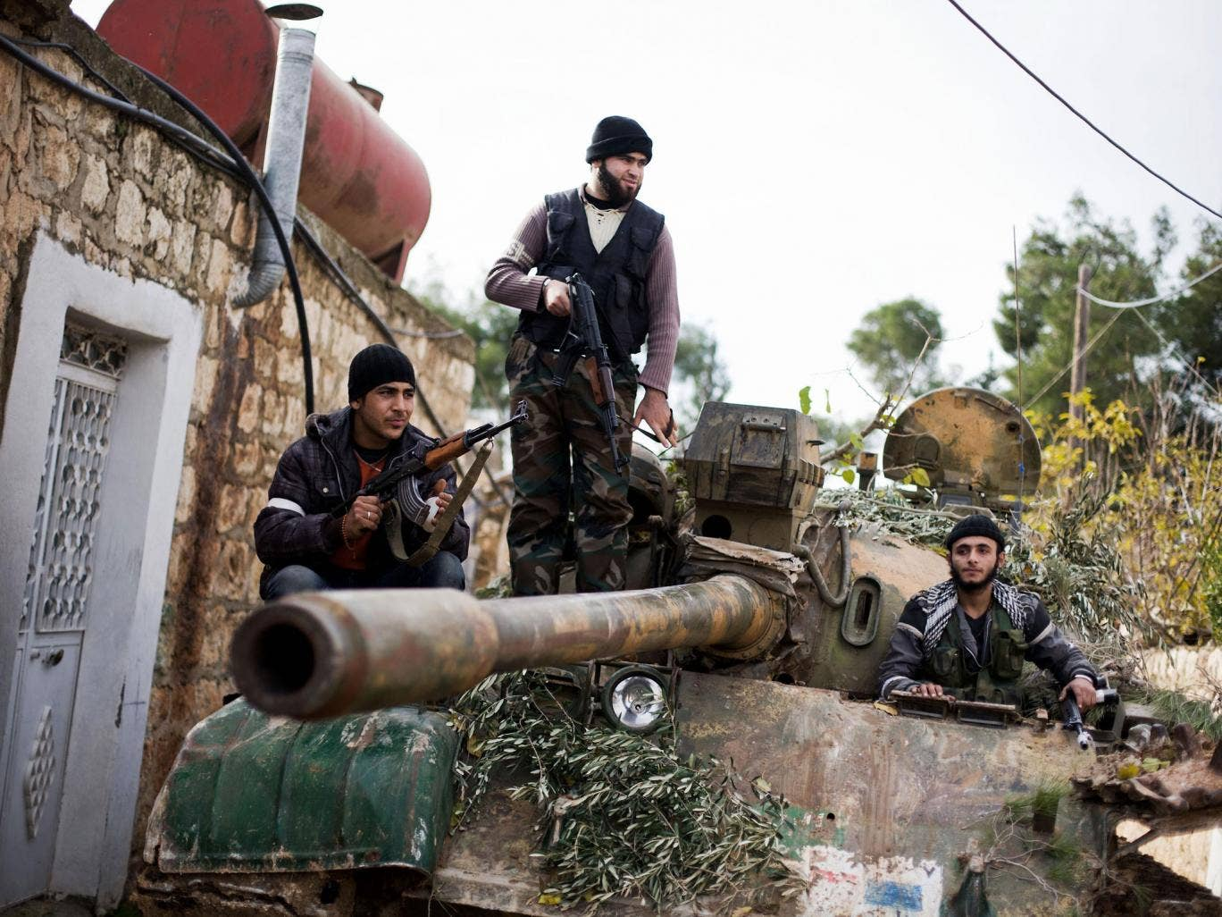 Kurdish members of the Free Syrian Army on a tank stolen from regime forces in the north of Aleppo province