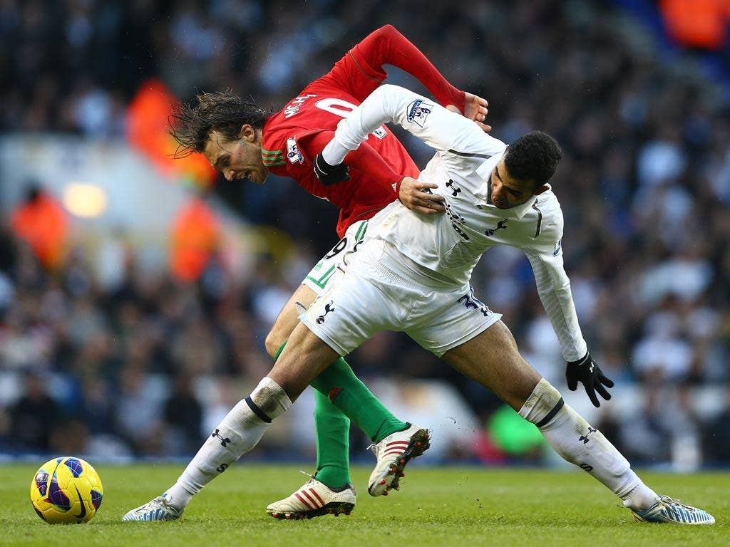 Michu battles with Sandro for the ball