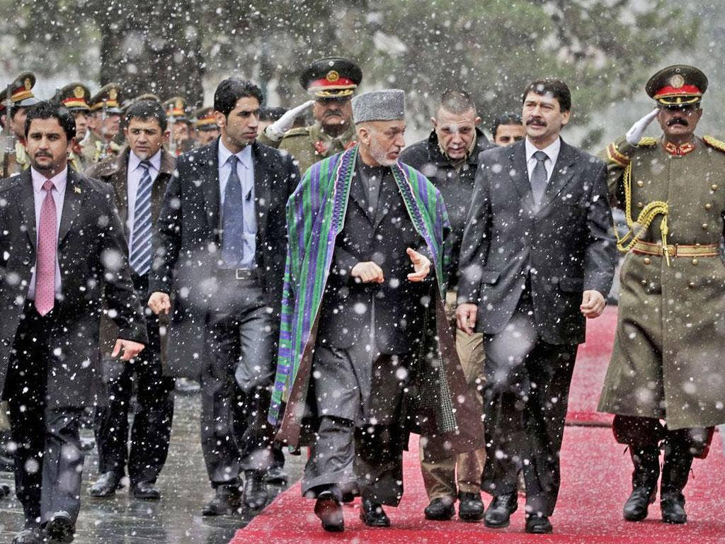 Hungarian President Janos Ader, second right, looks at guards of honor with Afghan President Hamid Karzai after his arrival at the presidential palace in Kabul, Afghanistan