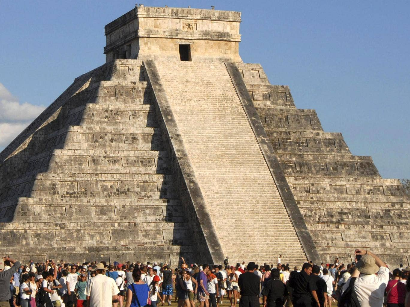 Tourists gather underneath the pyramid of Chichen Itza in Merida, southern Mexico