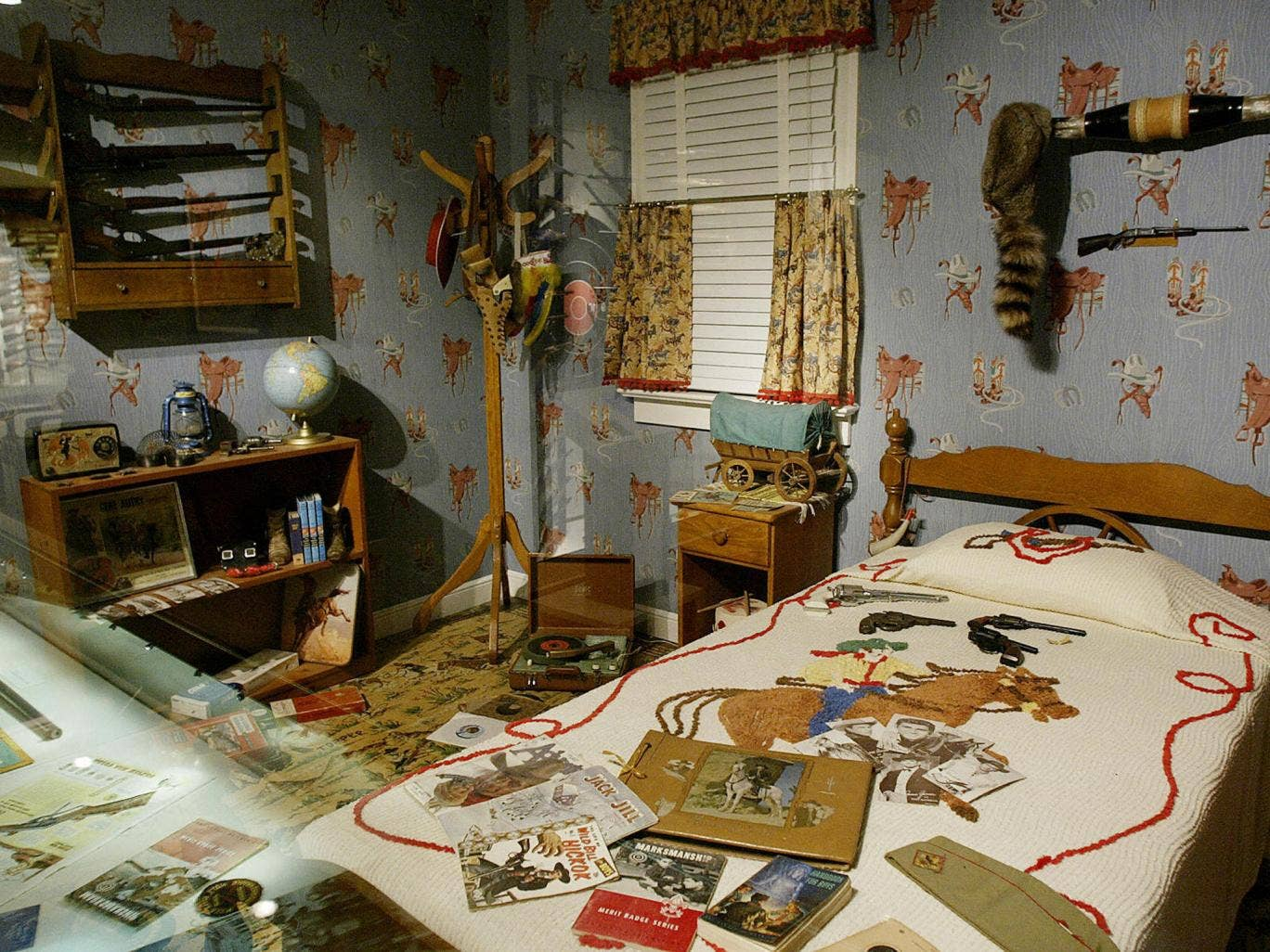 FAIRFAX, UNITED STATES: An exhibit showing a decades old boys room complete with toy guns on the bed and real guns designed for children on the wall