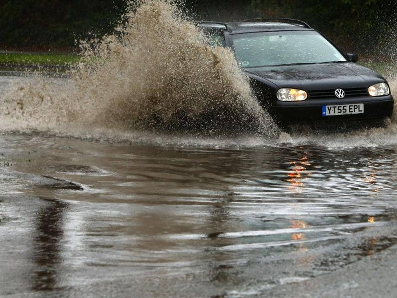 A motorist drives his car through flood waters in Chichester, West Sussex
