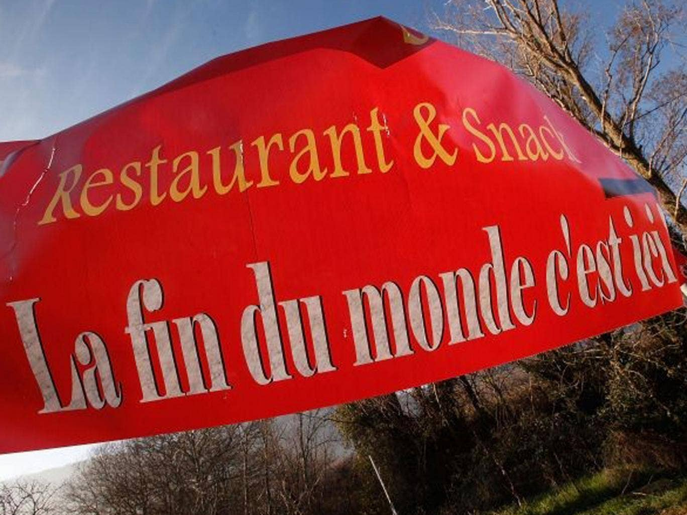 A sign, reading 'The end of the world, is here', advertises a restaurant in Bugarath, France, the small village said to be the only place on Earth which will be saved from this evening's apocalypse