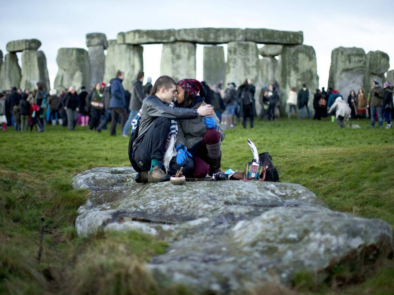 People embrace by the ancient stone circle of Stonehenge, in southern England, as access to the site is given to druids, New Age followers and members of the public on the annual Winter Solstice on 21 December 2012 AP Photo/Matt Dunham