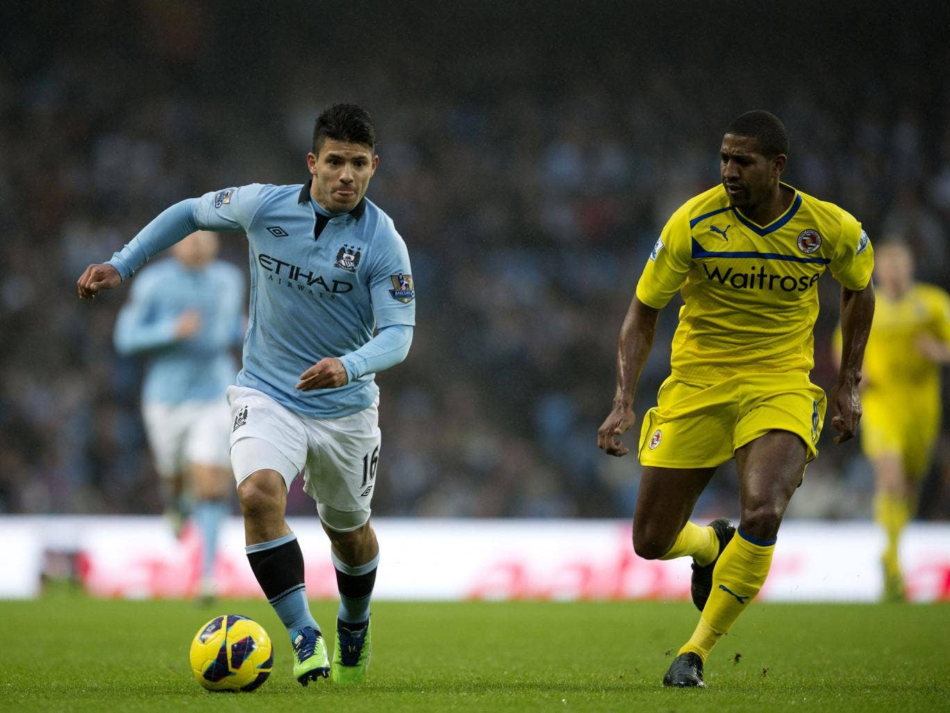 Manchester City's Argentinian striker Sergio Aguero (C) runs with the ball against Reading