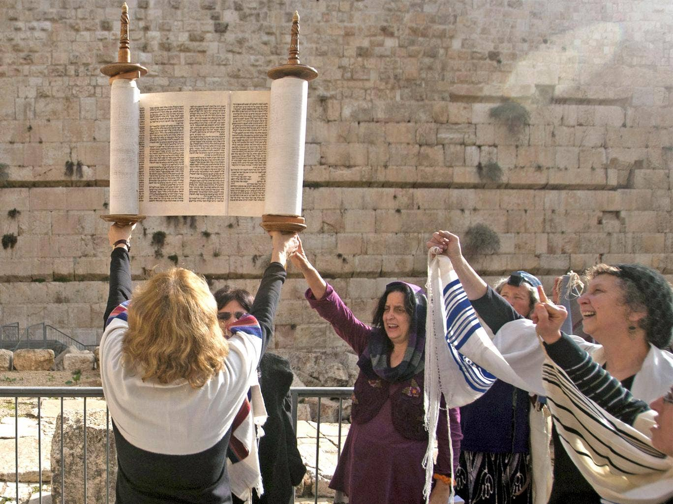 Israeli protesters hold a Torah and pray near the Western Wall