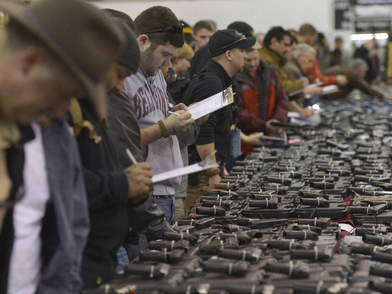 Gun enthusiasts fill out their background check paperwork while shopping for handguns at the Nation's Gun Show at the Dulles Expo Center in Chantilly, Virginia.