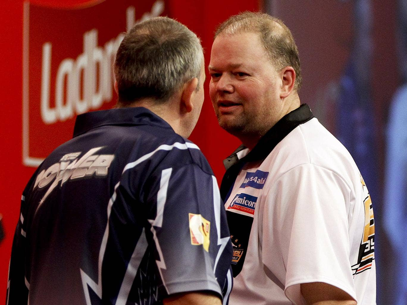 Raymond van Barneveld (right) and Phil Taylor clash during their semi final match on day fourteen World Darts Championship