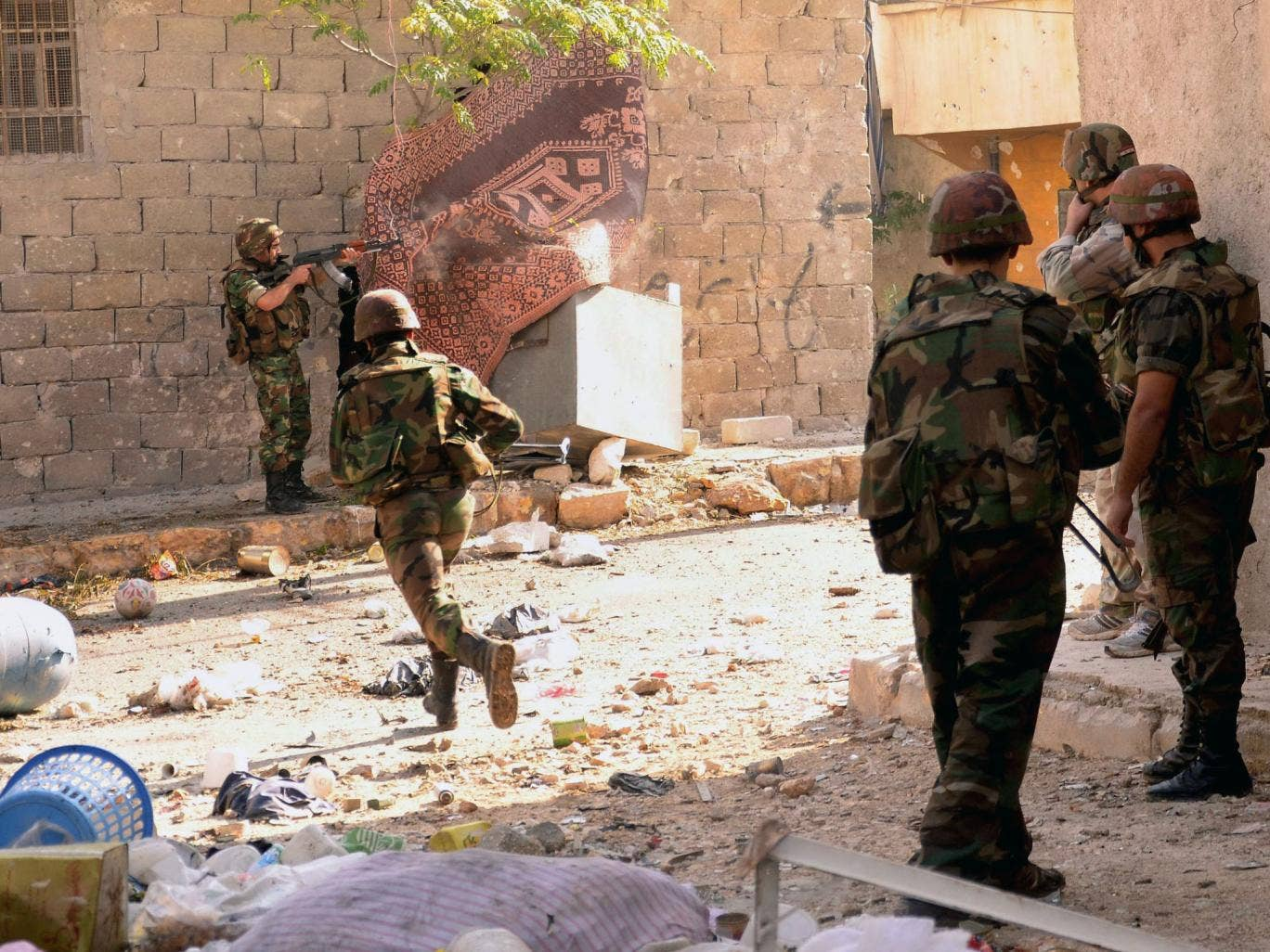 A Syrian army soldier runs across the street as others open fire during clashes with opposition fighters in the Tal al-Zarazi neighbourhood of the northern Syrian city of Aleppo on November 13, 2012.