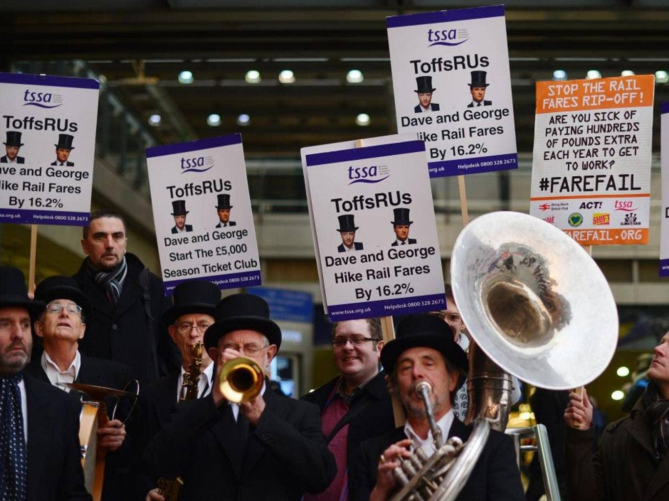 The 'ToffsRUs' jazz band play during a demonstration against a hike in rail fares at Kings Cross station in central London
