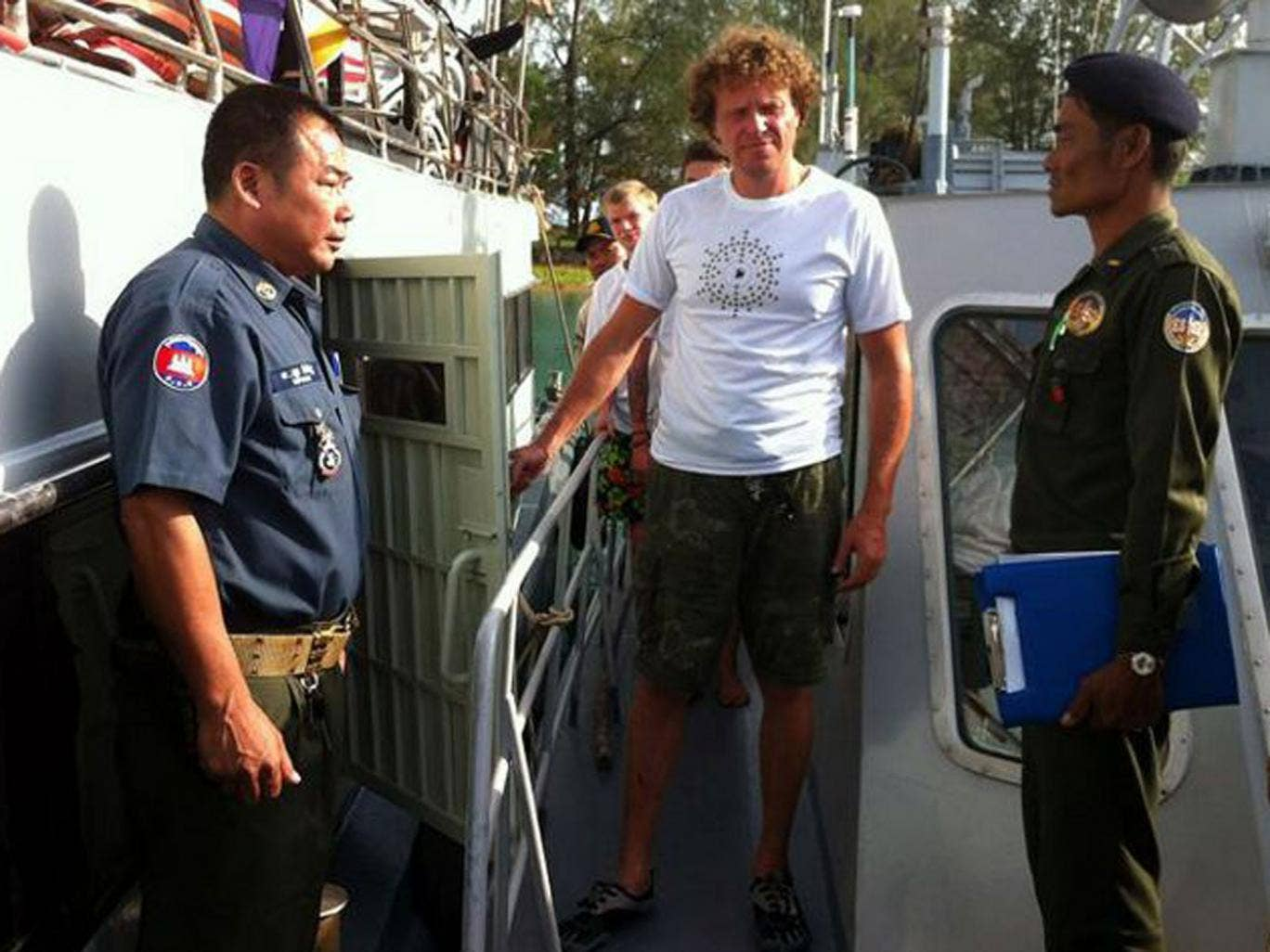 Sergei Polonsky (centre) is led away by Cambodian officials