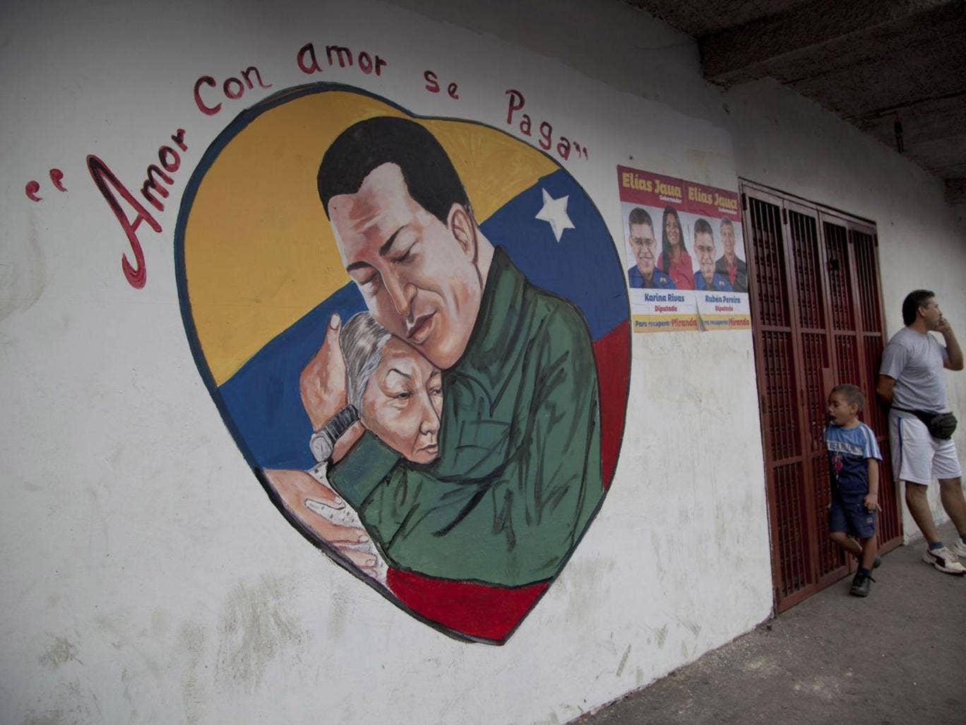 A heart-shaped mural shows an image of Venezuela's President Hugo Chavez hugging a woman, in Caracas