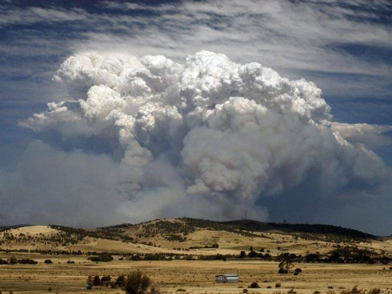Smoke from a bushfire billows over hills near Forcett, about 25 kilometres (16 miles) east of Hobart