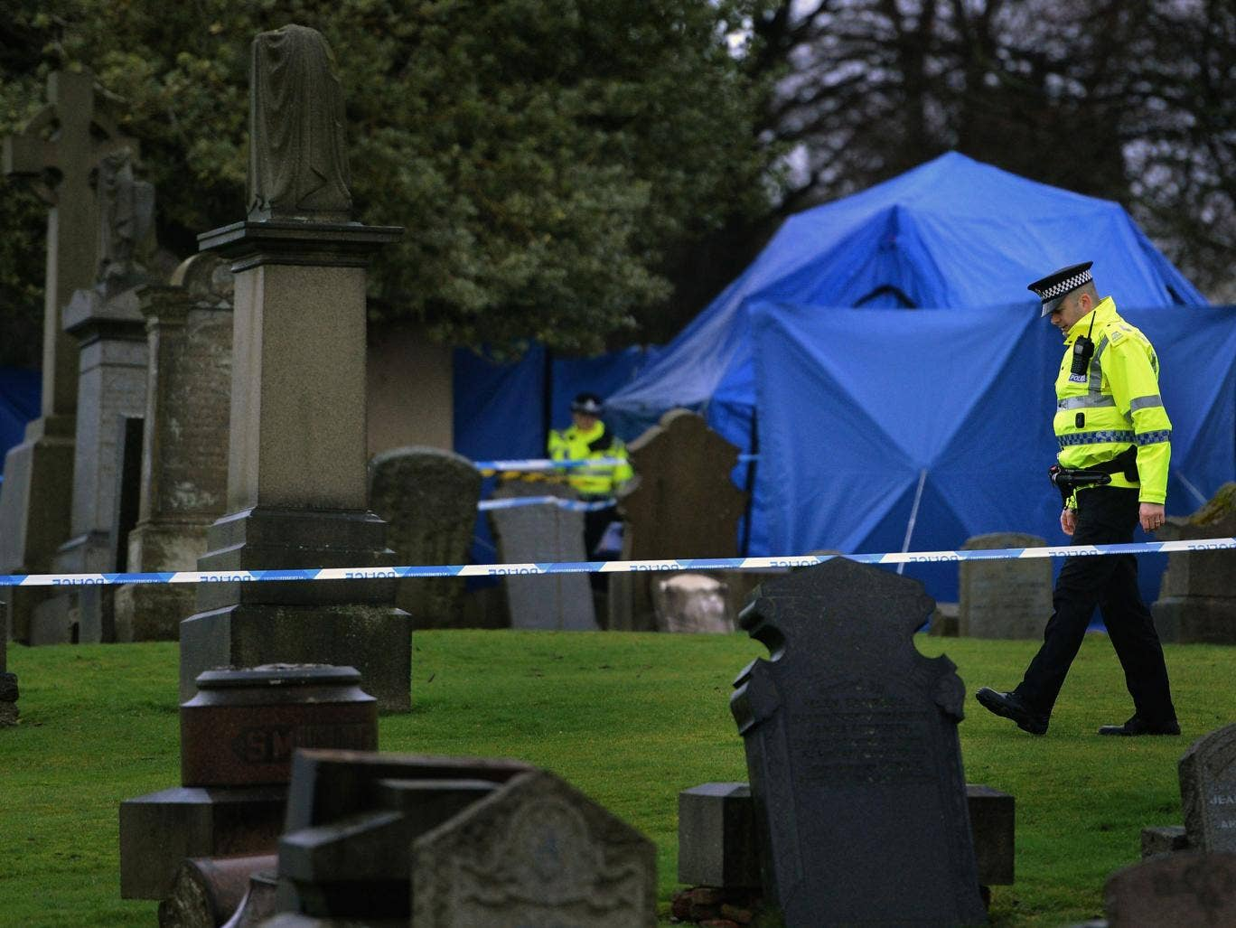 Police officers patrol Monkland Cemetery as forensic officers  start examining a burial plot