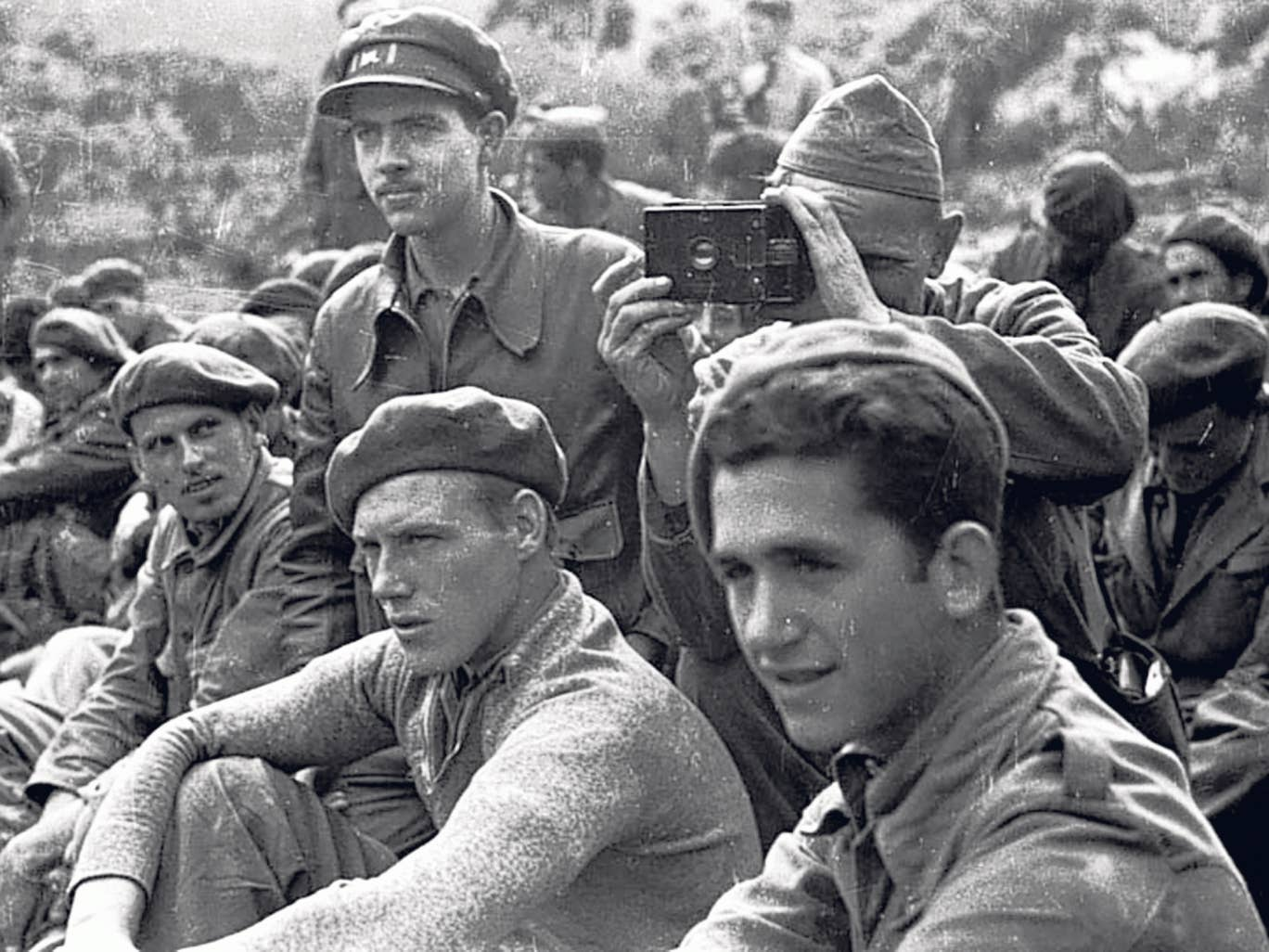 Randall, standing, left: 'We found ourselves acting as runners, ammunition carriers, guards, observers,' he said of his photographic unit
