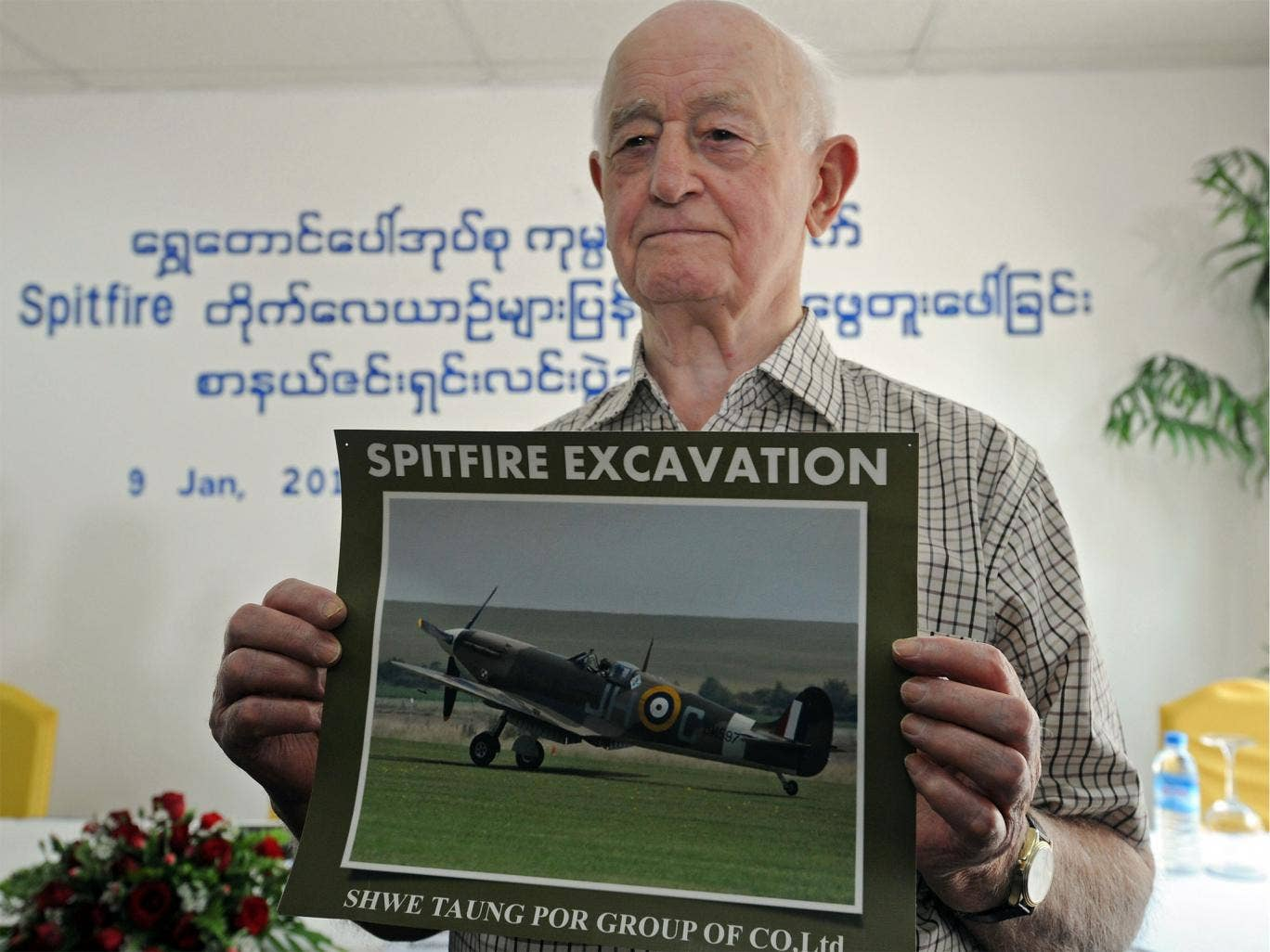 Stanley Coombe, a 91-year-old former British soldier, poses with a photo of a Spitfire