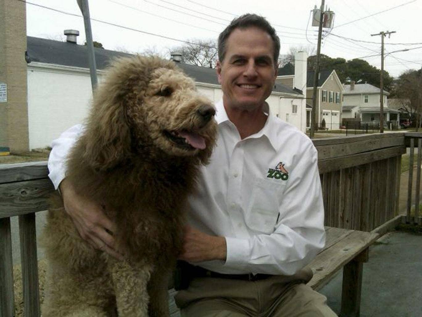 Virginia zoo's executive director Greg Brockheim with Charles the Monarch, a Labradoodle with a cut resembling the shaggy mane and tawny coat of a Lion