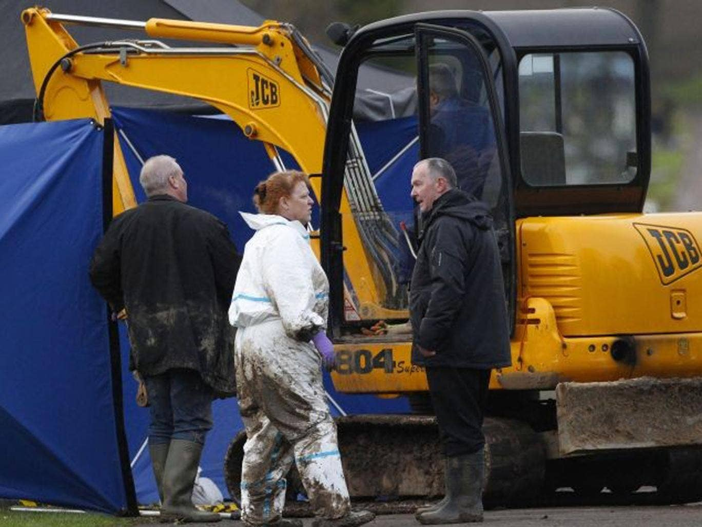 Forensic anthropologist Sue Black speaks with colleagues during the exhumation