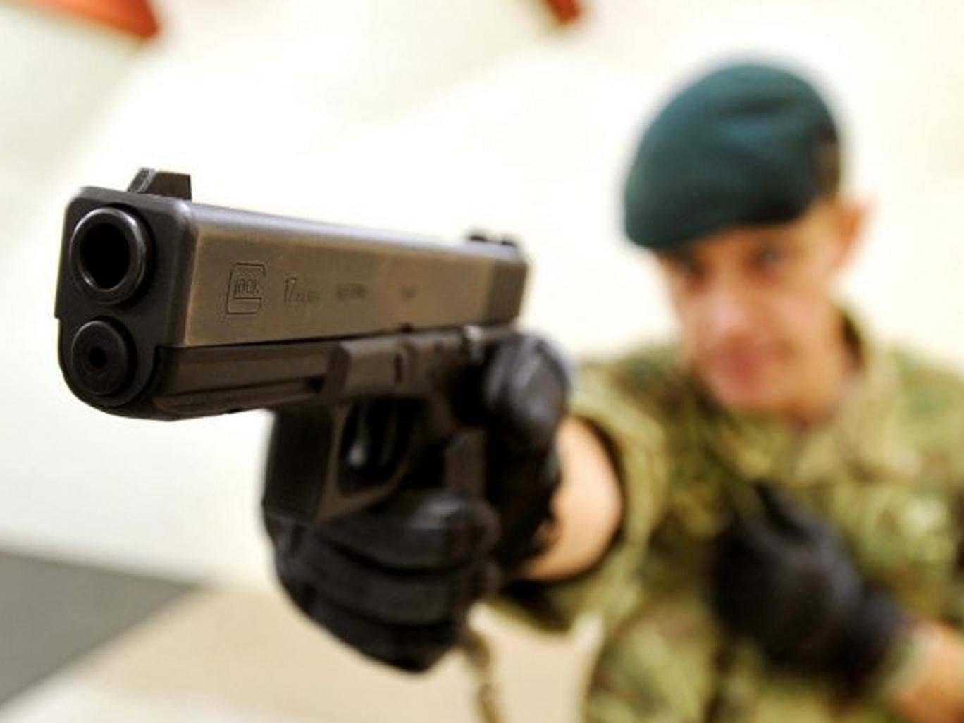 Royal Marine Sergeant Steve Lord tests a Glock 17 9mm pistol, on an indoor shooting range at Woolwich Barracks, south-east London, as personnel from all three services are to start using the new Glock pistols after a contract was awarded to replace the cu