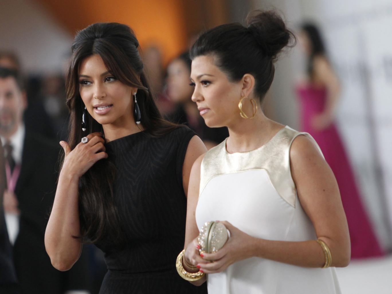 Kim (L) and Kourtney Kardashian arrive at the 20th Annual Elton John AIDS Foundation Academy Awards