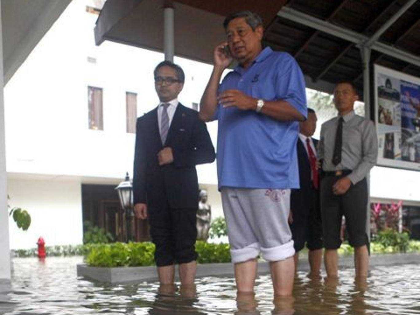 Indonesian president Susilo Bambang Yudhoyono, centre, inspects the flooded palace with foreign minister Marty Natalegawa, left, in Jakarta