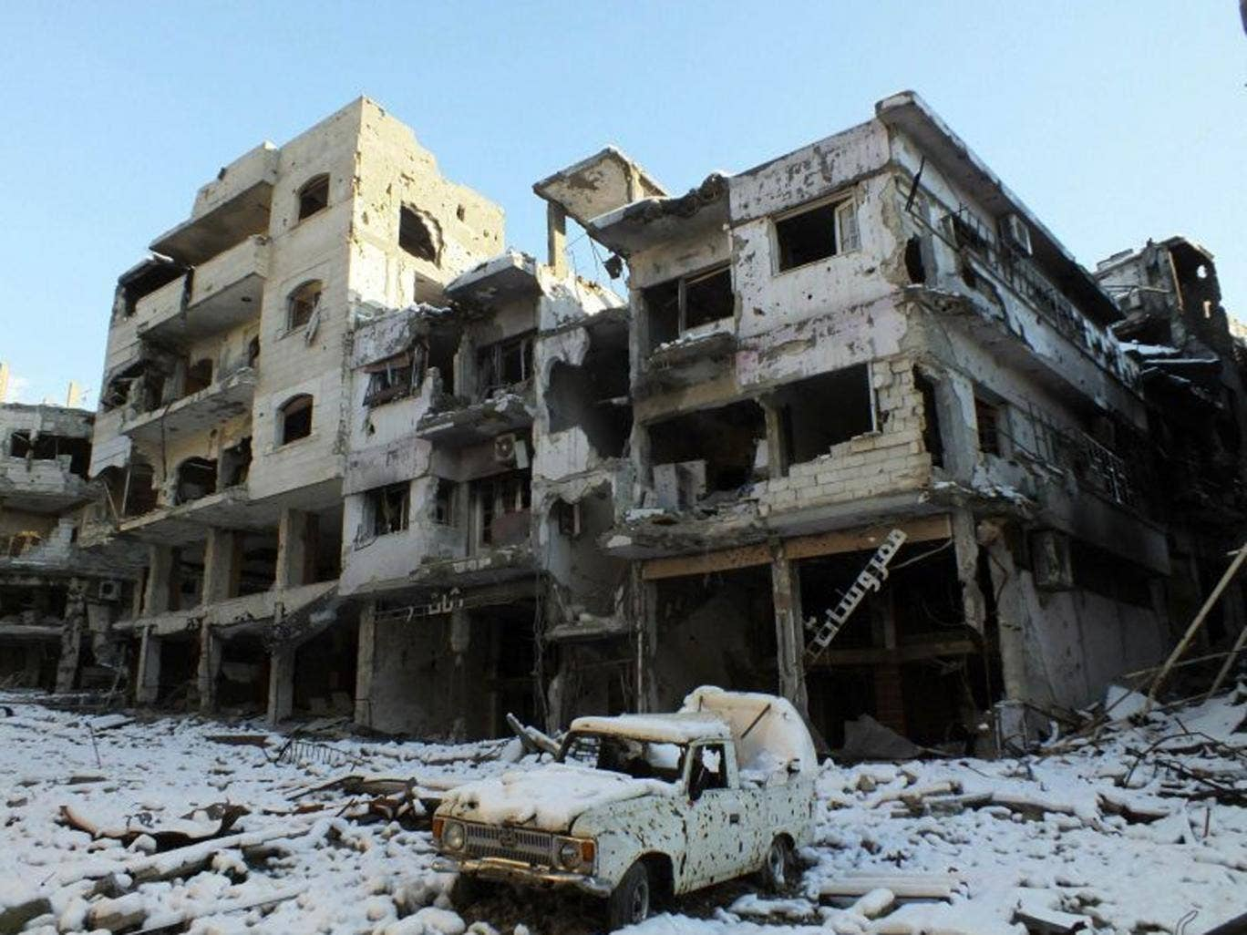 A damaged car and buildings covered with snow are seen at Jouret al Shayah area in Homs